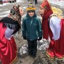Девушки в русских народных костюмах с маленьким посетителем праздника Масленицы в Сокольниках